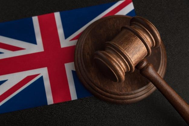 Sędzia gavel i flaga wielkiej brytanii. prawo i sprawiedliwość w wielkiej brytanii. naruszenie praw i wolności w wielkiej brytanii.