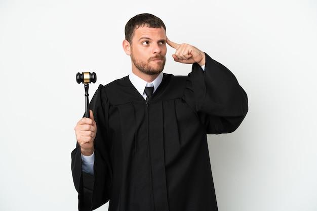 Sędzia kaukaski mężczyzna na białym tle na białej powierzchni, mający wątpliwości i myślący