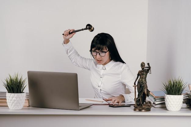 Sędzia młoda kobieta wydaje werdykt w swoim biurze lub zdalnie.