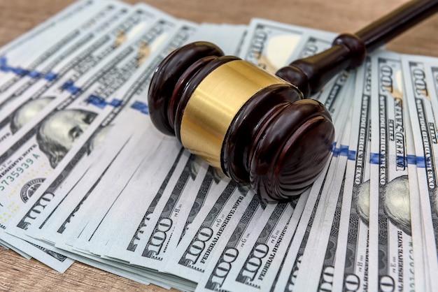 Sędzia młotek i dolarów na drewnianym stole z bliska