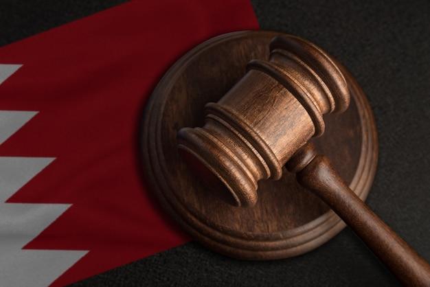 Sędzia młotek i flaga bahrajnu. prawo i sprawiedliwość w bahrajnie. naruszenie praw i wolności.