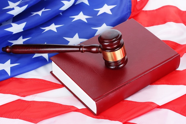 Sędzia młotek i książka na powierzchni flagi amerykańskiej