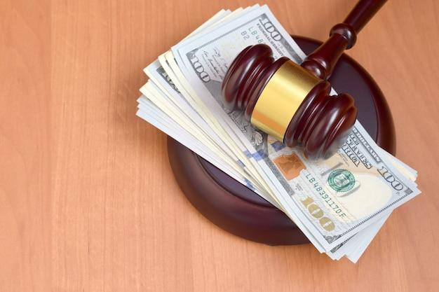Sędzia młotek i pieniądze na brązowy drewniany stół. wieleset banknotów dolarowych pod okiem sędziego na biurku sądu. wyrok i łapówka