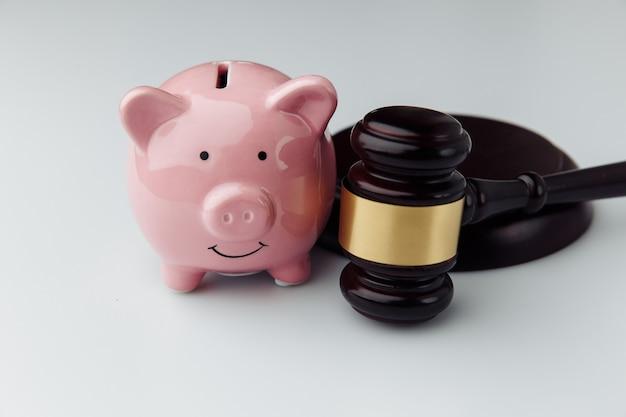 Sędzia młotek i różowa skarbonka na białym biurku z bliska. koncepcja kredytu i finansów