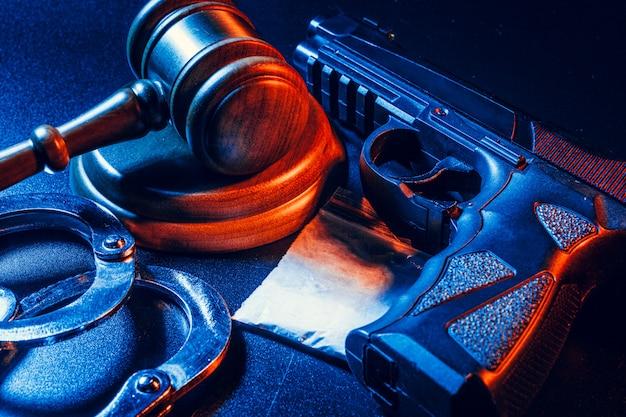 Sędzia młotek, kajdanki z białą torbą w proszku na ciemnym stole. pojęcie przestępczości, napadu, handlu narkotykami