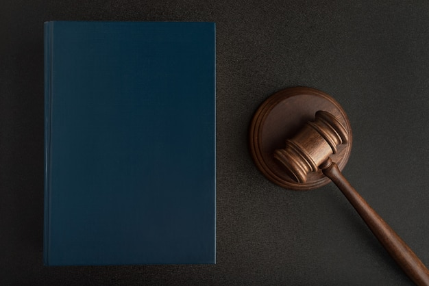 Sędzia młotek lub młotek i książki prawa na czarnej przestrzeni. prawoznawstwo. prawa i sprawiedliwość