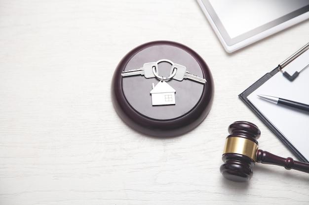 Sędzia młotek, model domu, klucze, schowek, tablet.