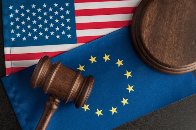 Sędzia młotek nad flagą usa i ue. konfrontacja prawna stany zjednoczone ameryki i unia europejska.