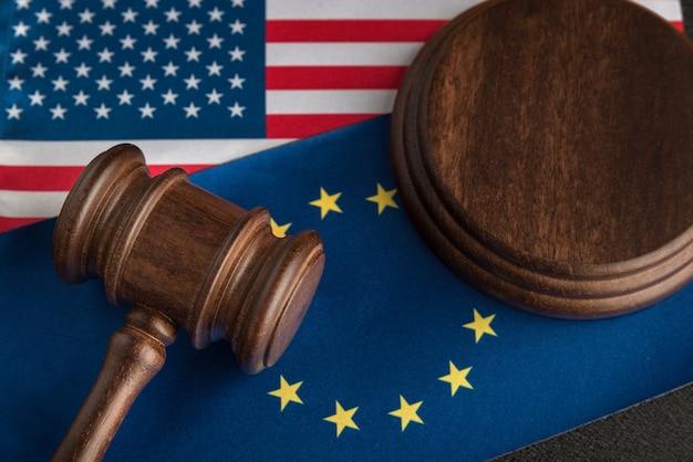 Sędzia młotek nad flagą usa i ue. wojna handlowa. konfrontacja prawna stany zjednoczone ameryki i unia europejska.