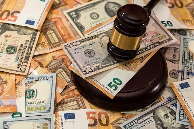 Sędzia młotek sędziego na banknocie dolara i euro. prawo