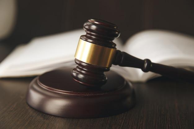 Sędzia młotek, szala sprawiedliwości i książki prawnicze w sądzie