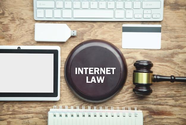 Sędzia młotek z innymi przedmiotami na drewnianym stole. prawo internetowe