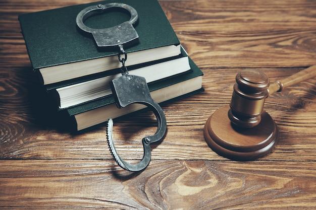 Sędzia młotek z książkami na drewnianym biurku