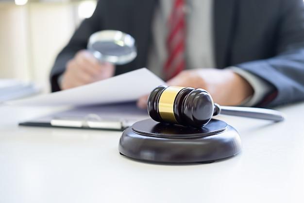 Sędzia młotek z prawnikami odbywającymi spotkanie zespołu w kancelarii prawnej.