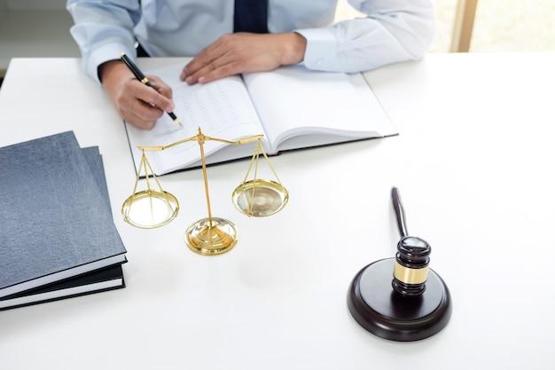 Sędzia młotek z wagą sprawiedliwości, prawników płci męskiej pracujących w firmie prawniczej w biurze