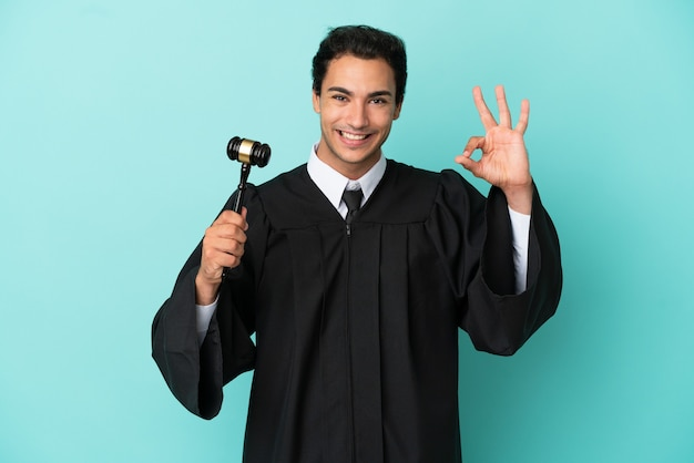 Sędzia na odosobnionym niebieskim tle pokazującym ok znak palcami