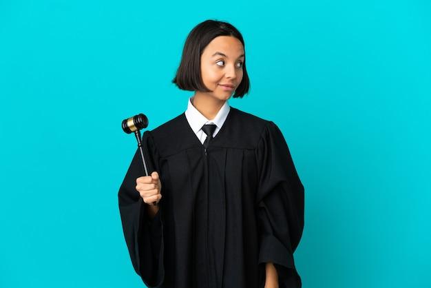 Sędzia na odosobnionym niebieskim tle, robiąc gest wątpliwości patrząc z boku