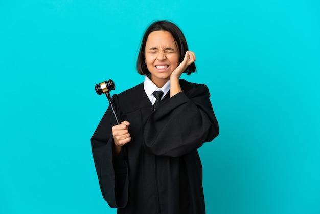 Sędzia na odosobnionym niebieskim tle sfrustrowany i zakrywający uszy