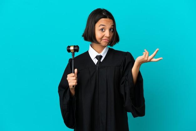 Sędzia nad odosobnioną niebieską ścianą, wykonując gest wątpliwości doubt