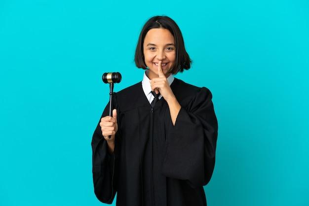 Sędzia nad odosobnionym niebieskim tłem pokazującym znak ciszy gestem wkładania palca do ust