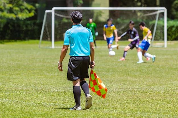 Sędzia piłkarski lub piłkarz sędzia oglądania meczu młodzieży chłopca