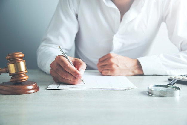 Sędzia piszący na papierze przy stole w sali rozpraw