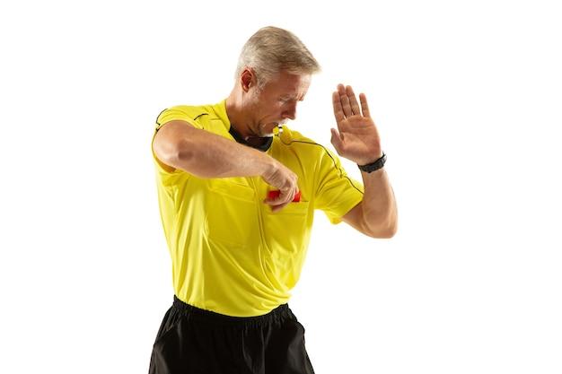 Sędzia pokazujący czerwoną kartkę i wskazujący na piłkarza lub piłkarza podczas gry na białym tle na białej ścianie. pojęcie sportu, łamanie zasad, kwestie kontrowersyjne, pokonywanie przeszkód.
