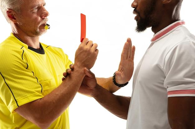Sędzia pokazujący czerwoną kartkę niezadowolonemu afroamerykańskiej piłce nożnej