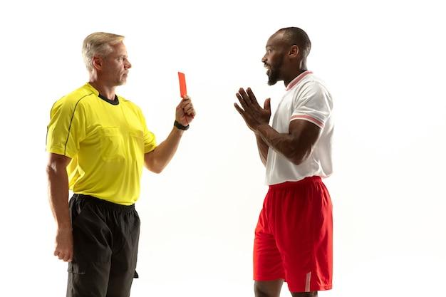 Sędzia pokazujący czerwoną kartkę niezadowolonemu afroamerykańskiemu piłkarzowi lub piłkarzowi podczas gry na białym tle na białej ścianie. pojęcie sportu, łamanie zasad, kontrowersyjne kwestie, emocje.
