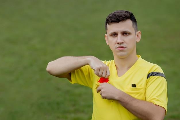 Sędzia pokazujący czerwoną kartkę niezadowolonemu piłkarzowi lub piłkarzowi podczas gry. pojęcie sportu, łamanie zasad, kwestie kontrowersyjne, pokonywanie przeszkód.