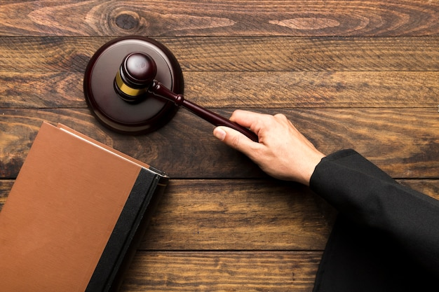 Sędzia ręcznie uderzający młotek na bloku brzmiącym