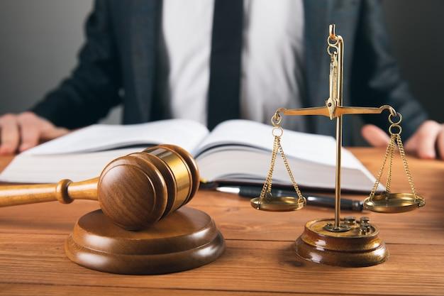 Sędzia robi notatki a na stole waga i młotek na szarej powierzchni