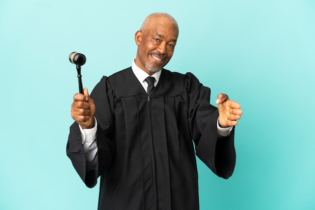 Sędzia starszy mężczyzna na białym tle na niebieskim tle, ściskając ręce za zamknięcie dobrej oferty