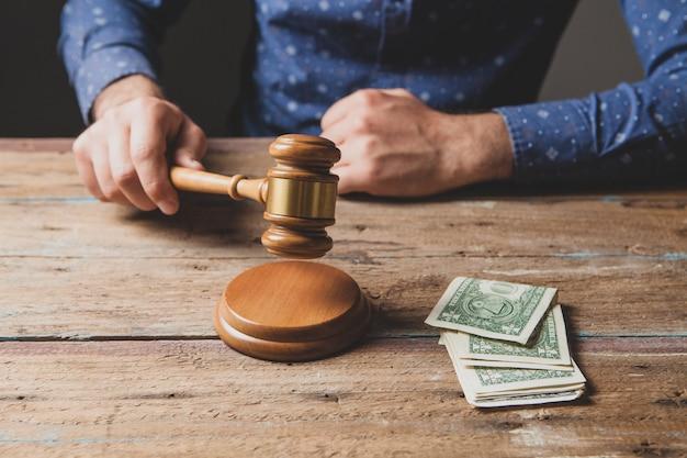 Sędzia uderza młotkiem i na stole są pieniądze