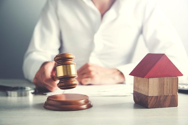 Sędzia z modelem domu uderza młotkiem przy biurku