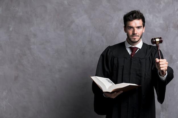 Sędzia ze średnim strzałem z książką i młotkiem