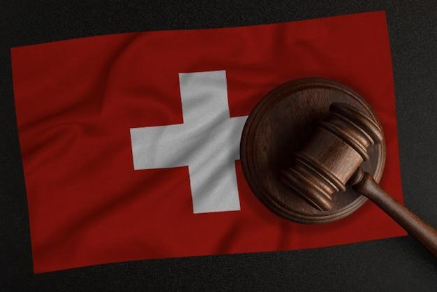 Sędziowie młotek i flaga szwajcarii. prawo i sprawiedliwość. prawo konstytucyjne.
