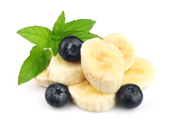 Segmenty banana z jagodami borówki i mięty na białym tle