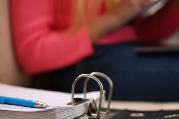 Segregator z dokumentami leży na kanapie młoda kobieta pracuje na laptopie