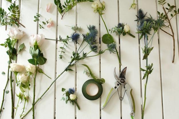 Sekator i inne narzędzia kwiaciarni i pokrojone świeże kwiaty leżące na białym drewnianym stole.
