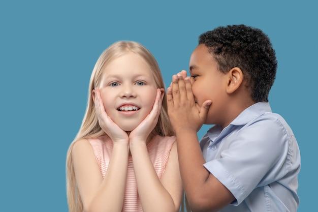 Sekret dla dzieci. afroamerykański chłopiec w wieku szkolnym szepcze do ucha zaskoczonej kaukaskiej słodkiej dziewczyny na niebieskim tle