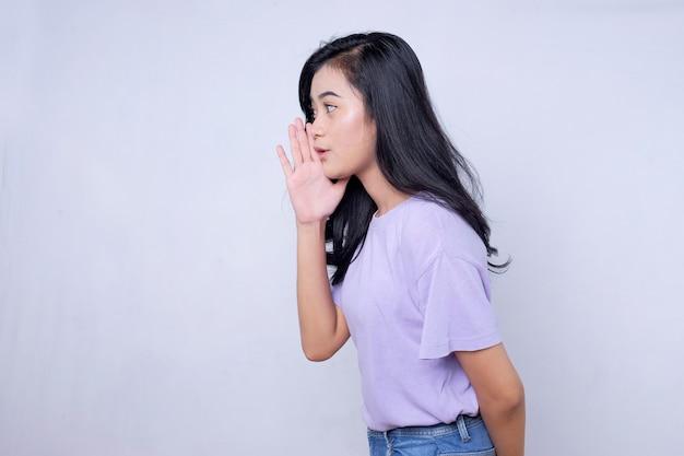 Sekret, koncepcja plotek. młoda kobieta szepcząc tajemnicę za jej ręką. kobieta biznesu na tle modnego białego studia