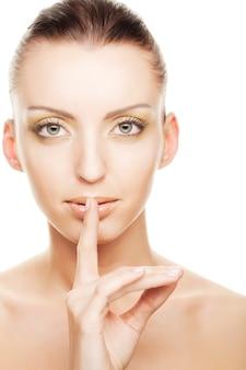 Sekret - młoda dziewczyna z palcem na ustach