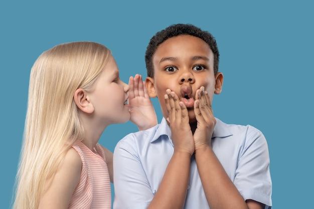 Sekret, niespodzianka. blondynka urocza dziewczyna szepcze sekret do ucha do zszokowanego ciemnoskórego chłopca z otwartymi ustami