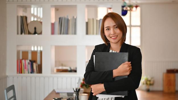 Sekretarek kobiety pracujące patrzeje kamerę.