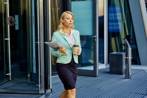 Sekretarka z dokumentami pije kawę na wynos na zewnątrz w pobliżu centrum biurowego