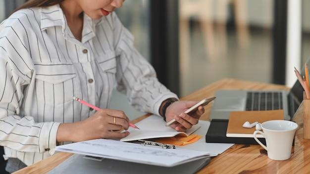 Sekretarz kobieta w białej koszuli w paski siedzi przy drewnianym biurku pisząc na notatniku i trzymając smartfon lewą ręką.