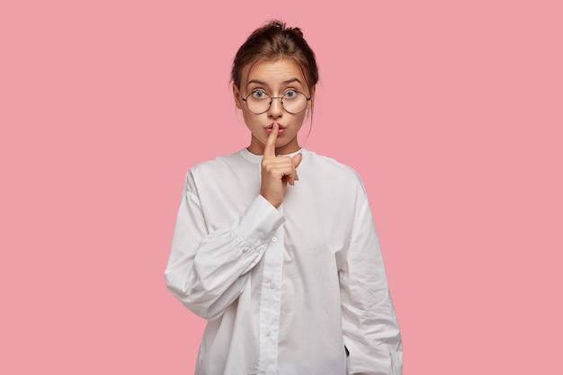 Sekretna młoda kobieta w okularach, pozowanie na różowej ścianie