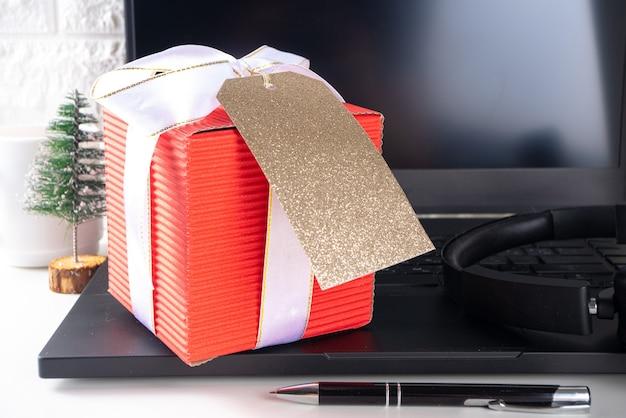 Sekretny mikołaj. obchody bożego narodzenia w biurze. biurko z laptopem, notatnikami, artykułami biurowymi, smartfonem i dużym pudełkiem prezentowym z świąteczną kokardką. flatlay