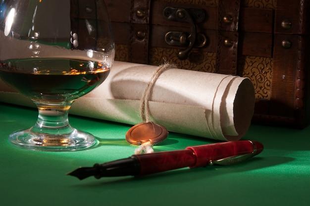 Sekretny zwój z pieczęcią woskową i szklanką koniaku na zielonym baize
